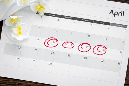 Concetto di ciclo mestruale. Calendario delle mestruazioni con assorbenti e fiori delicati sulla vista dall'alto del fondo di legno scuro Archivio Fotografico