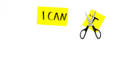 Self confidence concept. Cutting the letter t of written word I cant by scissor. White background top view copy space