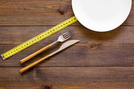 Diet for weight loss concept. Proper nutrition. Medical starvation. Empty plate with fork and knife near measuring tape on dark wooden background top view. Фото со стока