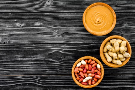 Peanut paste concept. Bowls with butter, nuts in shell, peeled nuts on black wooden background top view. Stock fotó