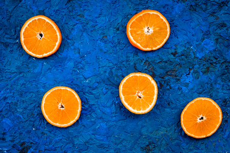 Oranges round slices pattern on blue background top view.