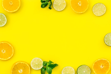Oranges and lime round slices pattern on yellow background top view. Banco de Imagens - 101346043