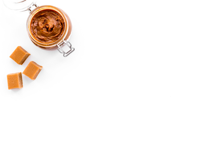 Caramel sauce in glass jar on white background top view.