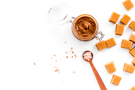 Salted caramel. Sauce in glass jar and caramel cubes on white background top view.