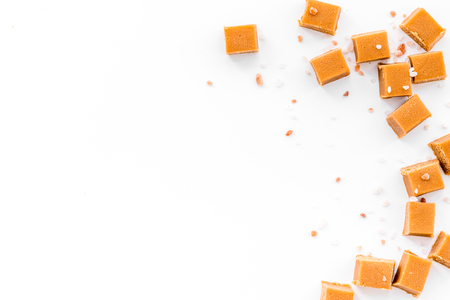 Salted caramel. Caramel cubes on white background top view.