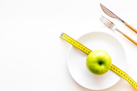 Proper nutrition with dietary fibre for weight loss. Apple on plate near measuring tape on white background top view. Stock Photo