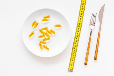 Dietary supplement for well-being. Fish oil or omega-3 capsules on plate near measuring tape on white background top view.