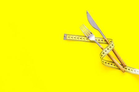 Diet, weight loss, slimming concept. Fork and knife with wound measuring tape on yellow background top view. 스톡 콘텐츠
