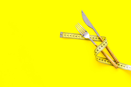 Diet, weight loss, slimming concept. Fork and knife with wound measuring tape on yellow background top view. Stock Photo