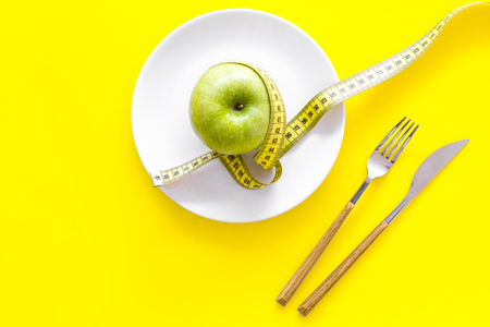 Proper nutrition with dietary fibre for weight loss. Apple on plate near measuring tape on yellow background top view. Stock Photo