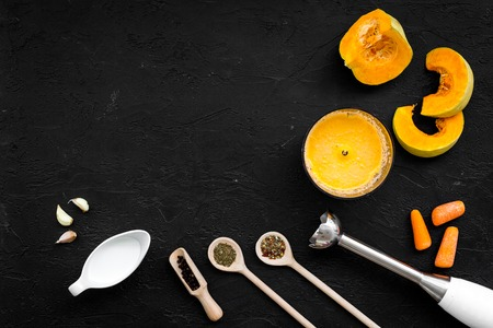 Cook orange cream soup with vegetables. Pumpkin, cream, spices, blender on black background top view.