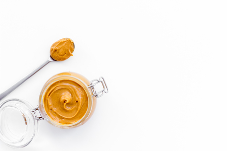 Nut butter, peanut butter in glass jar and spoon with butter on white background top view.