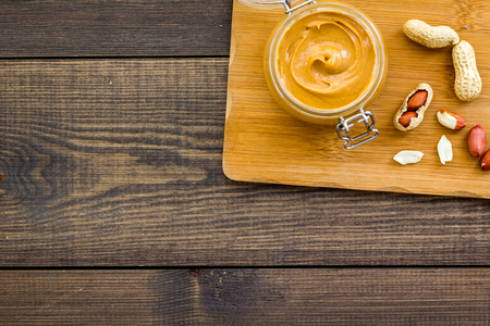 Make peanut butter. Paste in glass jar on cutting desk near peanut on dark wooden background top view. Stock fotó