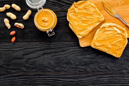 Make toast with nut paste. Two toasted, knife and glass jar with nut paste on black wooden background. Stock Photo