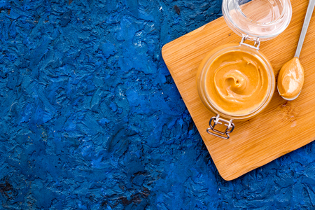 Nut butter in glass jar on blue background top view. Stock Photo
