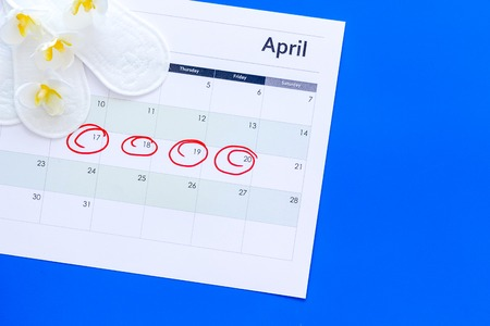 Menstruation cycle concept. Menstruation calendar with sanitary pads and delicate flowers on blue background top view.