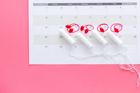 Menstrual period concept. Menstruation calendar with hygienic tampons and pills on pink background top view.