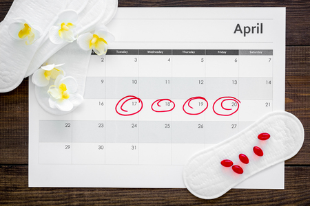 Menstruation cycle concept. Menstruation calendar with sanitary pads, contraceptive pills and delicate flowers on dark wooden background top view Stock Photo