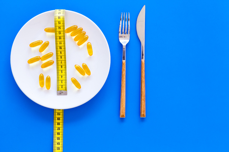 Pills or dietary supplement for weight loss. Treatment of obesity. Treatment of anorexia. Gold pills on plate near measuring tape on blue background top view. Фото со стока