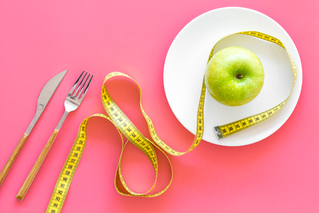 Proper nutrition with dietary fibre for weight loss. Apple on plate near measuring tape on pink background top view.