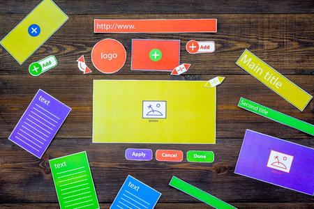 Developing internet site. Website design concept. Elements, blocks, instruments, tools for make site on dark wooden background top view.