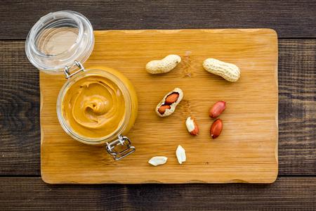 Make peanut butter. Paste in glass jar on cutting desk near peanut on dark wooden background top view