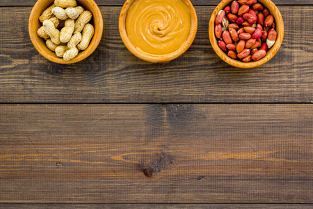 Peanut paste concept. Bowls with butter, nuts in shell, peeled nuts on dark wooden background top view.