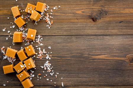 Trendy dessert. Salted caramel. Caramel cubes sprinkled by salt crystals on dark wooden background top view.