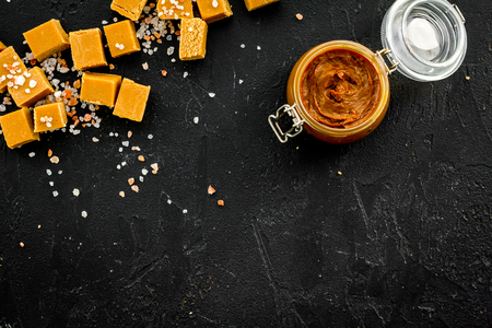 Contrast of flavors. The combination of salty and sweet. Caramel sauce in glass jar near caramel cubes on black background top view. 版權商用圖片
