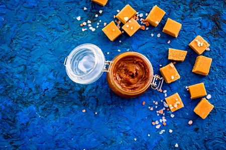 Contrast of flavors. The combination of salty and sweet. Caramel sauce in glass jar near caramel cubes on blue background top view.