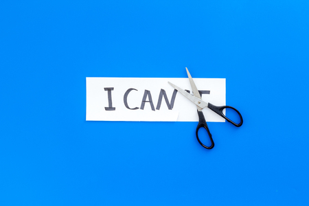 I can concept. Motivate yourself, believe in yourself. Scissor cut the letter t of written word I cant. Blue background top view.