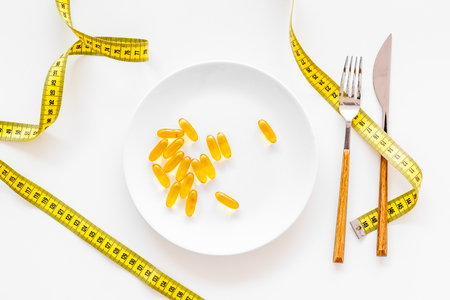 Dietary supplement for well-being. Fish oil or omega-3 capsules on plate near measuring tape on white background top view