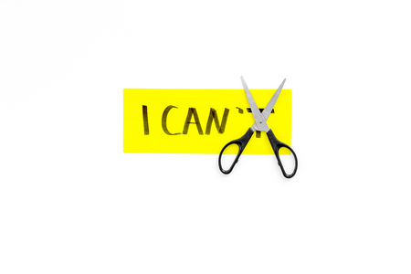 I can concept. Motivate yourself, believe in yourself. Scissor cut the letter t of written word I cant. White background top view copy space