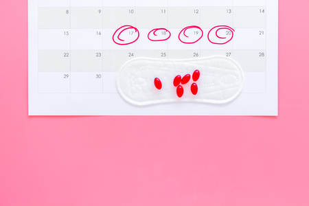 Menstruation cycle concept. Menstruation calendar with sanitary pads and contraceptive pills on pink background top view copy space