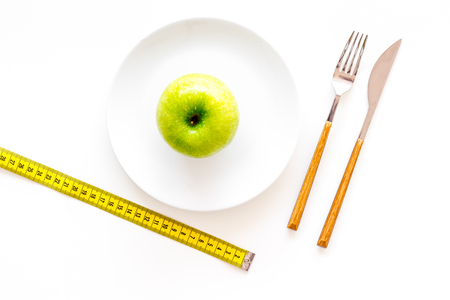 Proper nutrition with dietary fibre for weight loss. Apple on plate near measuring tape on white background top view Stock Photo