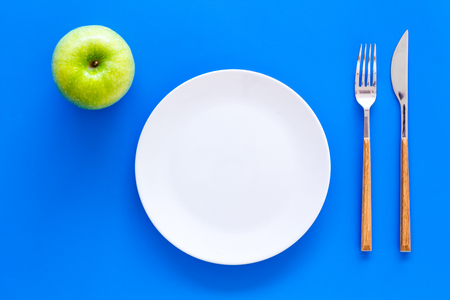 Proper nutrition with dietary fibre for weight loss. Apple on plate near measuring tape on blue background top view mockup
