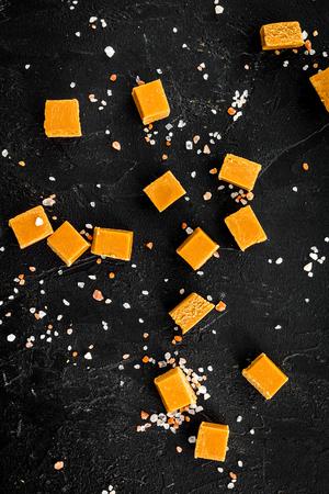 Trendy dessert. Salted caramel. Caramel cubes sprinkled by salt crystals on black background top view