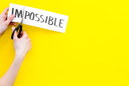 All is possible concept. Hands cutting the part im of written word impossible by scissor. Yellow background top view copy space