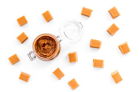 Caramel sauce in glass jar near caramel cubes on white background top view