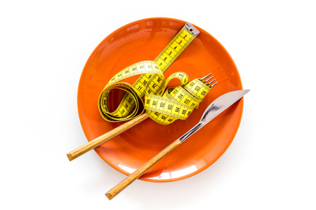 Diet for weight loss concept. Proper nutrition. Medical starvation. Empty plate with fork and knife near measuring tape on white background top view