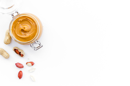 Peanut butter in glass jar near peanut on white background top view copy space