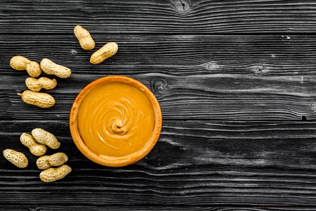 Product for hearty breakfast. High-calorie product. Peanut butter in bowl near nuts in shell on black wooden background top view copy space Stock Photo