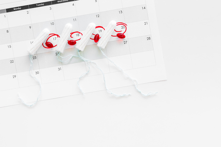 Menstrual period concept. Menstruation calendar with hygienic tampons and pills on white background top view space for text Stock Photo