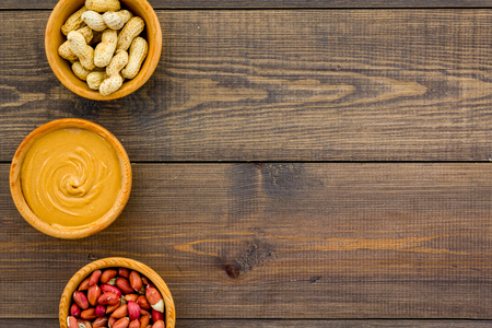 Peanut paste concept. Bowls with butter, nuts in shell, peeled nuts on dark wooden background top view copy space