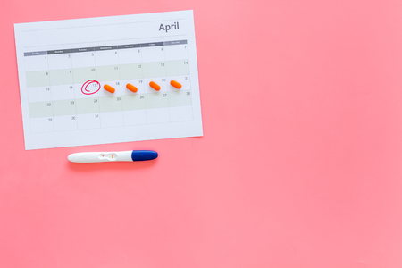 Planning pregnancy. Positive pregnancy test near calendar page and pills on pink background top view copy space