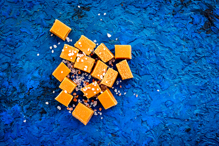 Trendy dessert. Salted caramel. Caramel cubes sprinkled by salt crystals on blue background top view copy space 免版税图像