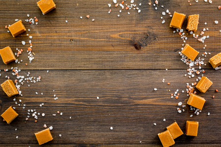 Trendy dessert. Salted caramel. Caramel cubes sprinkled by salt crystals on dark wooden background top view space for text