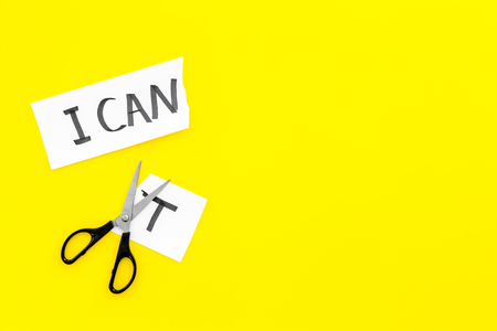 I can concept. Encourage yourself. Scissors cut off the letter t of written word I cant. Yellow background top view copy space Stok Fotoğraf