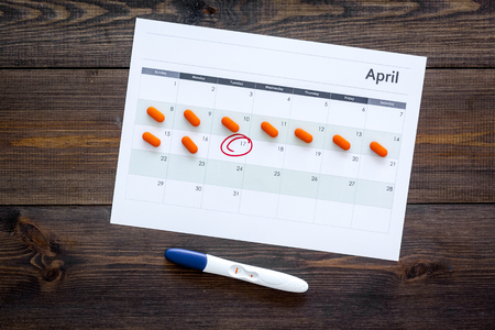 Planning pregnancy. Positive pregnancy test near calendar page and pills on dark wooden background top view Stock Photo