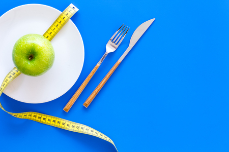 Proper nutrition with dietary fibre for weight loss. Apple on plate near measuring tape on blue background top view copy space